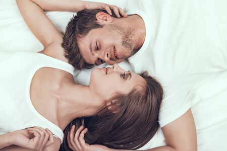 Honeymoon Couple is Lying in Bed and Smiling.