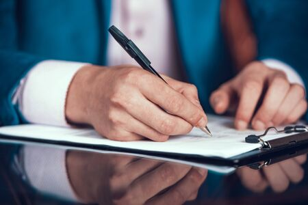 Cropped Photo of Man in Suit Putting Signature. Standard-Bild