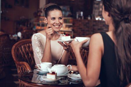 Happy Women Have Tea and Cake in Restaurant. Standard-Bild