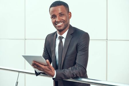 African Businessman Working on Tablet and Smiling. Standard-Bild