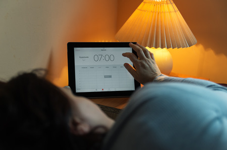 Man setting the alarm on tablet before going to sleep