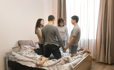 Parents with children praying and holding hands on the bed Reklamní fotografie