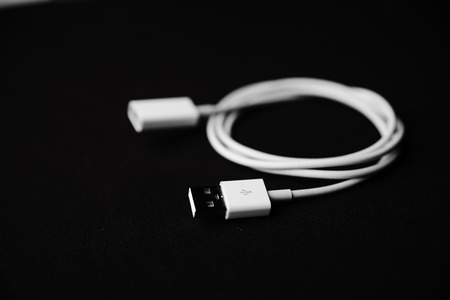 Mobile smartphone usb charger on dark background Фото со стока