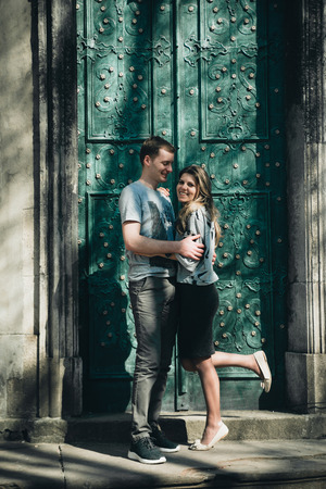 Stone walls in ancient town background. Passionate hugs of young couple on the stairs near a beautiful building with old doors