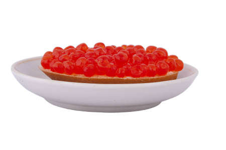 Bread with red caviar on plate on white background photo