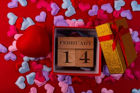 Wooden cubes with the inscription February 14 inside a gift box and hearts on a red background