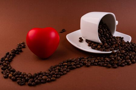 Cup with coffee beans on a brown background and a heart