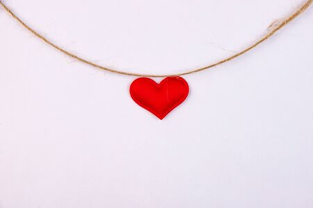 Red heart hanging on a linen thread on a white background 版權商用圖片