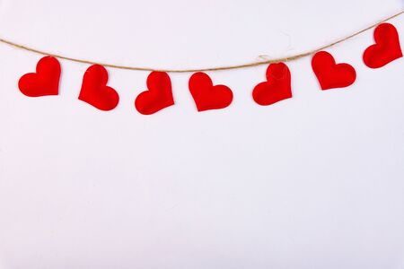 Red hearts hanging on a linen thread on a white background