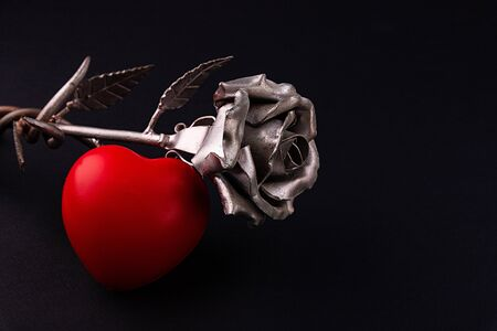 A thin bronze rose made by forging from metal. Red volumetric heart nearby.