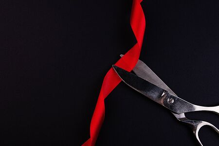 Scissors cutting a red ribbon depicting an inauguration , launch, opening or start of an official ceremony