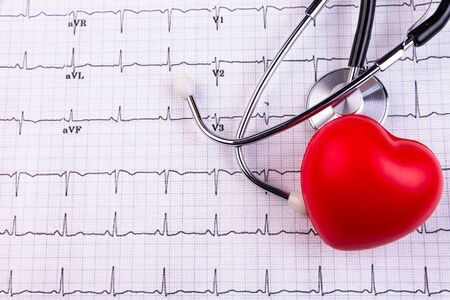 Stethoscope and red heart lying on cardiogram. Healthcare, cardiology and mediacal concept Stock Photo