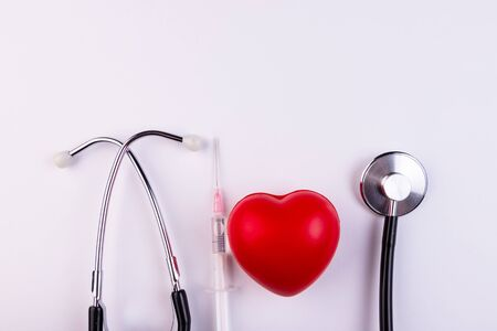 A stethoscope, a syringe and a red heart lie on a white background. Healthcare, cardiology and media concept.