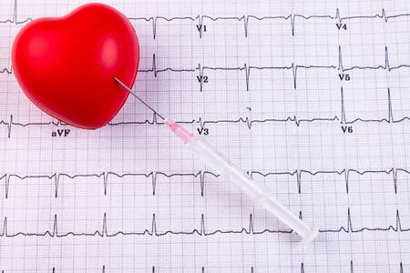 A syringe and a red heart lie on a cardiogram. Healthcare, cardiology and media concept. Stock Photo