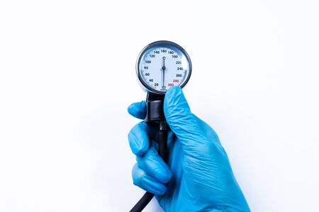 Medical professional, nurse or doctor holds in hand, wearing blue medical glove, sphygmomanometer showing level of diastolic and systolic blood pressure on white background. Concept for hypertension