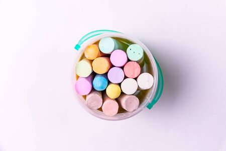 Colored chalk in a bucket on a white background