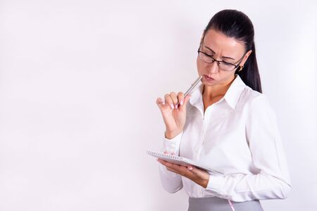 Portrait of a thoughtful young woman with glasses looking in a notebook isolated on a white background Foto de archivo - 138299647