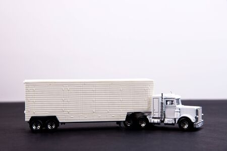 Toy truck on a black table with a white place for inscription
