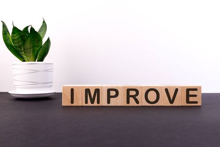 Improve word concept on wooden blocks on a black table with a green flower on a white background