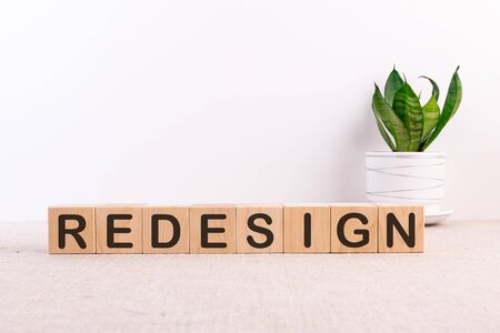 REDESIGN word made with building blocks on light background