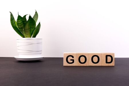 Good waxing, word on wooden cubes on a dark table with a flower and a light background