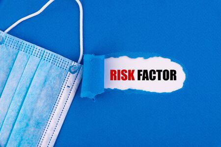 The text Risk Factor appearing behind torn blue paper. 스톡 콘텐츠