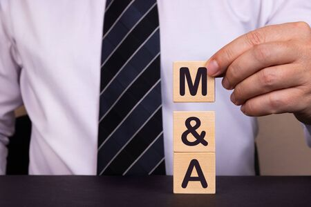 Man made words Mergers and Acquisitions with wood blocks.