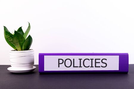 policies office folder lies on a dark table with a flowerpot and a flower on a light background Stock Photo