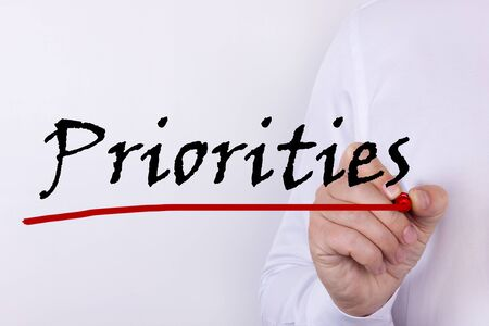 Businessman hand writing Priorities with marker, Business concept Stock Photo