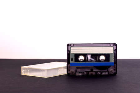 Retro audio cassette tape from the 80s on a black background.