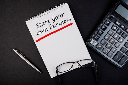 Vue de dessus du mot Démarrez votre propre concept d'entreprise écrit dans un cahier avec stylo et calculatrice.