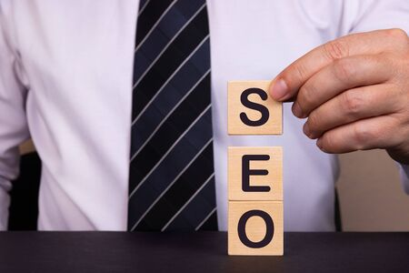 Businessman made word SEO with wood building blocks.