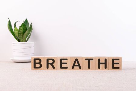 Breathe concept words on a light table and a light background on wooden cubes
