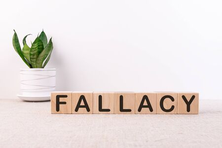 FALLACY word on cubes on a light table with a flower and a light background