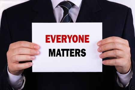 Businessman holding a card with text everyone matters