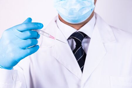 Doctor in blue gloves holds a medical syringe for injection 스톡 콘텐츠