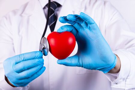 Doctor with stethoscope holding a heart close up