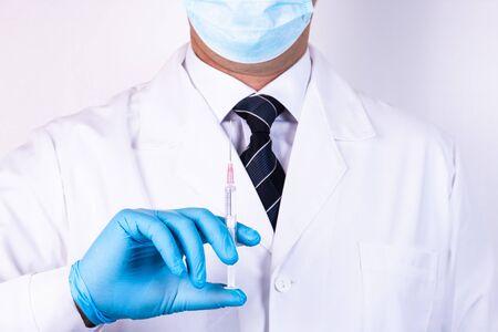 Doctor in blue gloves holds a medical syringe for injection Stock fotó