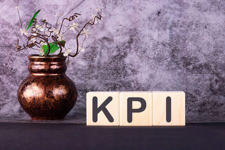 CONCEPT KPI inscription on wooden cubes on a grey background Banco de Imagens