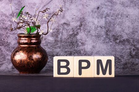 Word BPM made with wood building blocks on a grey background