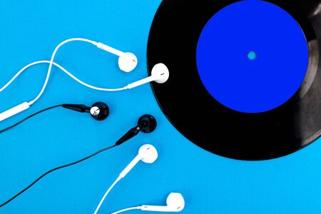 Vinyl record and headphone on a blue background. Audio enthusiast,music lover or professional DJ equipment