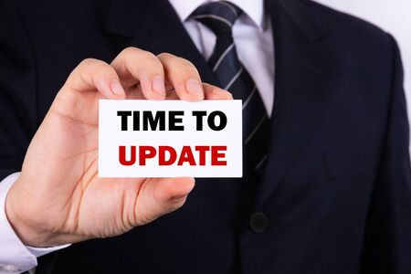 Businessman holding a card with text Time to update