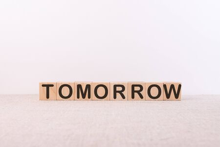 Word TOMORROW made from wooden cubes on a light background