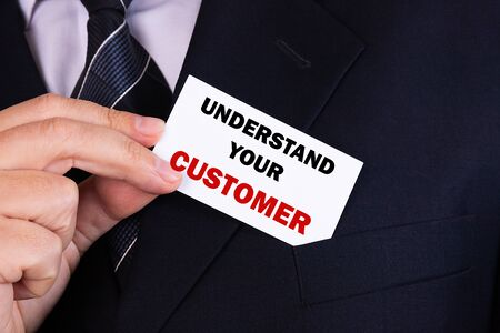 Businessman putting a card with text understand your custome in the pocket Stockfoto