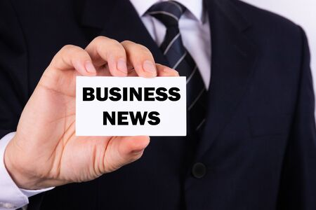 Businessman holding a card with text Business news 版權商用圖片