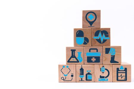 Pyramid of wooden blocks with healthcare medical icons. Insurance your health concept.