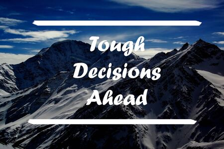 Tough Decisions Ahead written against the backdrop of snowy mountains and blue sky. Inspirational motivation quote.