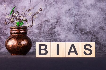 Word BIAS made with wood building blocks on a gray background