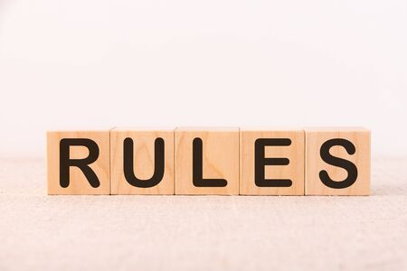 RULES word concept written on wooden cubes blocks lying on a light table and light background