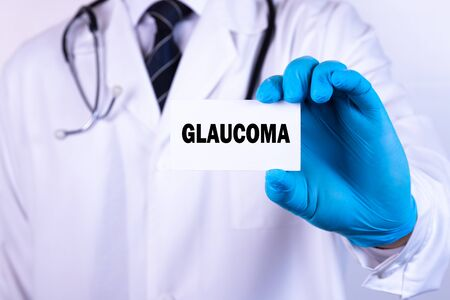 Doctor holding a card with text Glaucoma medical concept Zdjęcie Seryjne